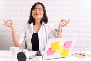 Vrouw met yoga handen aan bureau probeert te ontspannen tussen spannende dingen