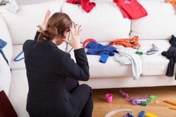Vrouw zit op de grond en ziet een chaos van kleren die staan voor haar heftige gevoel